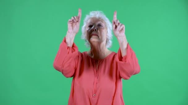 Portrait einer älteren Frau, die in die Kamera blickt und eine Herzensgeste mit ihren Händen zeigt und einen Luftkuss sendet. Grauhaarige Großmutter in roter Bluse auf grünem Bildschirm im Studio. Nahaufnahme.