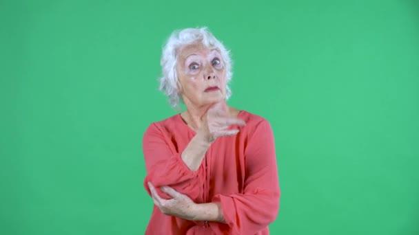 Portrait einer älteren Frau, die in die Kamera blickt, jemanden schimpft und mit dem Zeigefinger droht. Tun Sie diese Geste nicht. Grauhaarige Großmutter in roter Bluse auf grünem Bildschirm im Studio. Nahaufnahme.