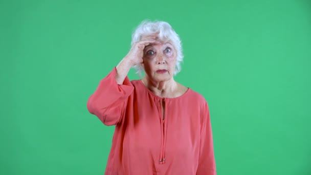 Porträt einer älteren Frau, die konzentriert und glücklich darüber nachdenkt, dass es eine Idee gibt. Grauhaarige Großmutter in roter Bluse auf grünem Bildschirm im Studio. Nahaufnahme.