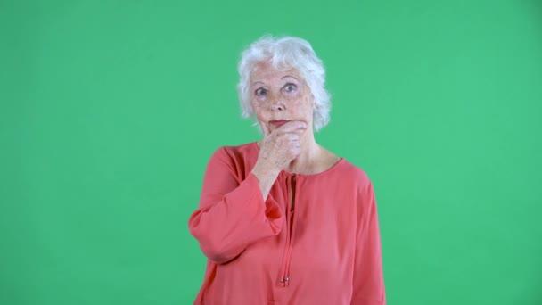Porträt einer älteren Frau, die konzentriert denkt, stört keine Ahnung. Grauhaarige Großmutter in roter Bluse auf grünem Bildschirm im Studio. Nahaufnahme.