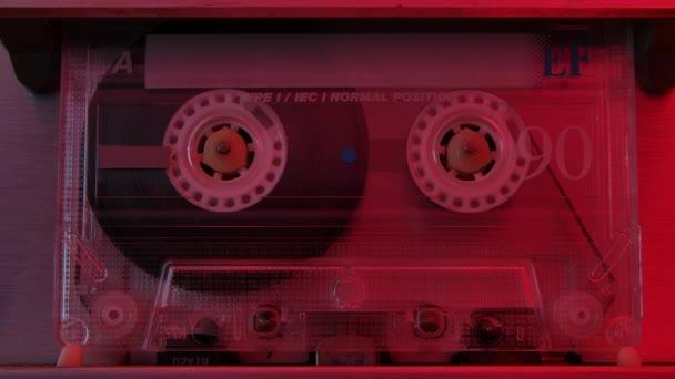 Retro kompakt audio kazetta játszik extrém közelről. Vintage zenei kazetta játszik vissza a játékos megvilágított piros neon fények. Lassú mozgás..
