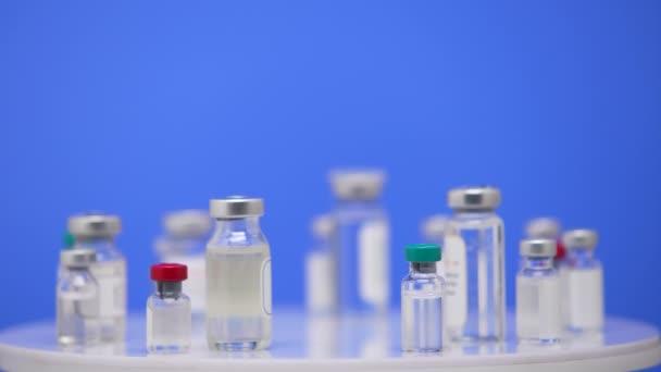 Coronavirus-Impfstoff in Ampullen in Großaufnahme auf einem Labortisch blauen Hintergrund. Pharmakologische Medikamente gegen die Pandemie Covid-19. Medizinischer Impfstoff von 2019-ncov. Blue Screen, Chroma Key. Aus nächster Nähe. Langsam.