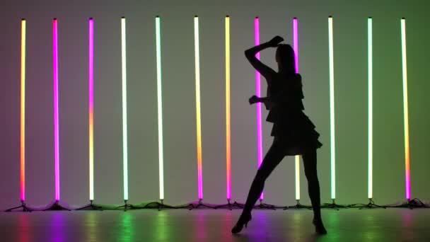 Professionelle schlanke Tänzerin tanzt Rumba im Studio vor der Kulisse heller, bunter Neonlichter. Das Mädchen arbeitet die Schritte des Tanzes aus. Silhouette. Zeitlupe.