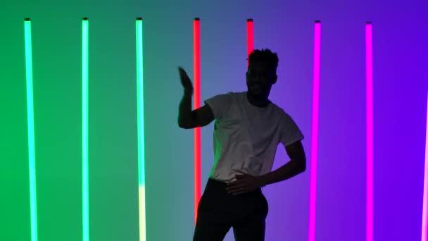 Soloauftritt einer professionellen Standardtänzerin. Schwarzer Mann, der Salsa vor dem Hintergrund bunter Lichter im Studio tanzt. Aus nächster Nähe. Zeitlupe.
