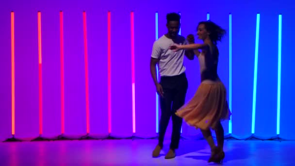 Happy black man and caucasian woman practice streak and spins in the background of multicolored neon lights. Passionate Latin American salsa dance in slow motion.