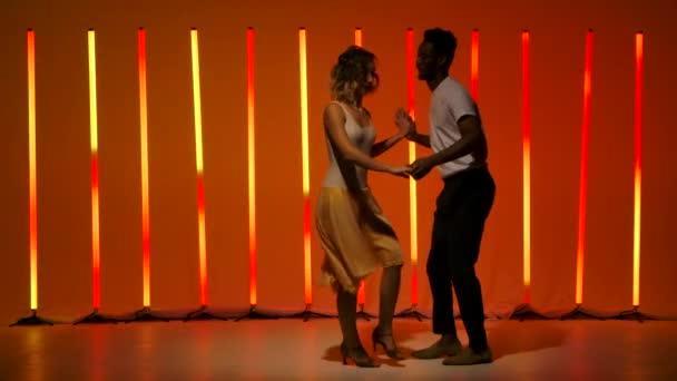 Ein wunderschönes sinnliches Paar führt leidenschaftliche Tanzschritte von Hispanics vor einem leuchtend rot-orangen Neonhintergrund vor. Ein Mann und eine Frau tanzen Salsa in Zeitlupe.