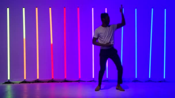 Soloauftritt einer professionellen Standardtänzerin. Schwarzer Mann tanzt Salsa vor dem Hintergrund mehrfarbiger Neonlichter im Studio. Zeitlupe.