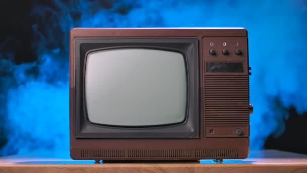 Stará televize na dřevěném stole na zakouřeném pozadí studia s modrými neonovými světly. Brown retro mediální vybavení. Zpomalený pohyb.