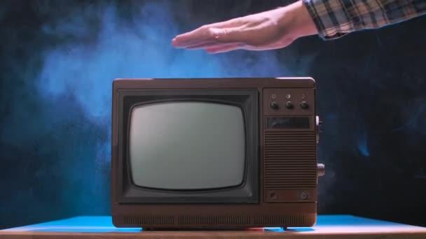 Az ember megpróbálja bekapcsolni a régi tévét, bekopogtat, porszemcséket szórva szét. Vintage televízió füstös stúdió háttérrel, kék neon fényekkel. Férfi kezek összezárva. Lassú mozgás..