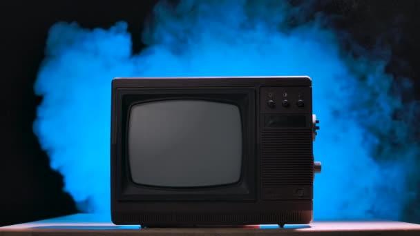 Stílus retro TV készlet kapcsolókkal. Régi stílusú TV füstös stúdió háttérrel, kék neon fényekkel és porszemcsékkel. Lassú mozgás..