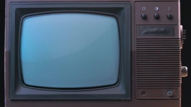 Brown Style retro TV set kapcsolókkal. Régi stílusú TV füstös stúdió háttérrel, kék neon fényekkel és porszemcsékkel. Lassú mozgás..