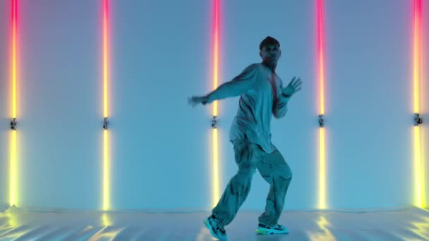 Cool young talented hip hop guy is dancing against the backdrop of bright neon lights, performing amazing gestures and movements. Street dance. Slow motion.