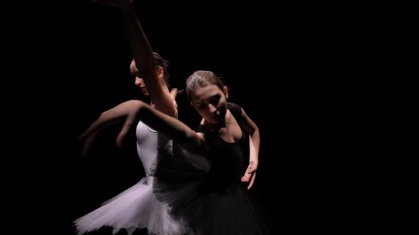 Camera rotates around two flexible ballerinas in black and white tutus move their hands dramatically against a backlit black studio background. Orbital shot. Close up. Slow motion.