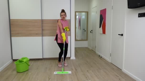 Hezká mladá žena utírá podlahu, pak flirtuje a hraje na mop jako na kytaru. Žena v domácnosti v domácím oblečení pózuje na pozadí světelné místnosti. Zpomalený pohyb.