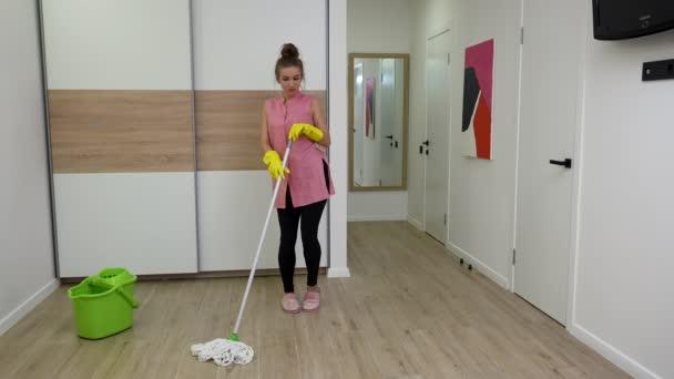 Hezká mladá žena utírá podlahu, nudí se a pak se baví a tancuje. Žena v domácnosti v domácím oblečení pózuje na pozadí světelné místnosti. Zpomalený pohyb.