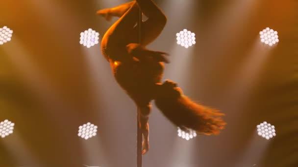 Fiatal táncos sport rúd tánc végez trükköket rúd. Fitness koncepció a nők számára. Silhouette egy karcsú atlétikai test egy fekete füstös stúdió háttér sárga világítással. Közelről..
