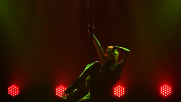 Sexy blondýna v obleku se točí na tyči, ukazuje pružnost a smyslně hladí její tělo. Erotický tanec, striptýz v tmavém studiu na pozadí jasných světel. Silueta. Zavřít.
