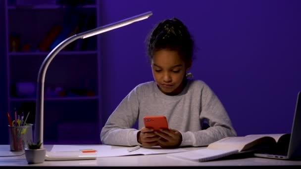 Das Mädchen wirft ihren Stift auf ihr Notizbuch, greift zum Telefon, blättert in Nachrichten, sagt überrascht wow. Ein Mädchen sitzt an einem Tisch im Licht einer Nachtlampe. Aus nächster Nähe. Zeitlupe bereit 59.97fps.