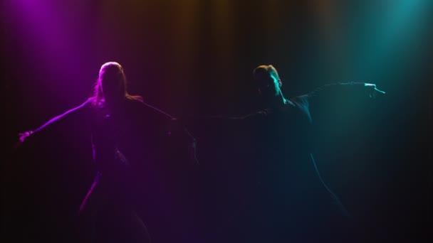 Die Silhouette eines tanzenden Paares tritt aus Dunkelheit und Rauch hervor. Mann und Frau tanzen leidenschaftlich Rumba-Elemente vor dem Hintergrund der wunderschönen blauvioletten Strahlen des Studiolichts. Nahaufnahme.