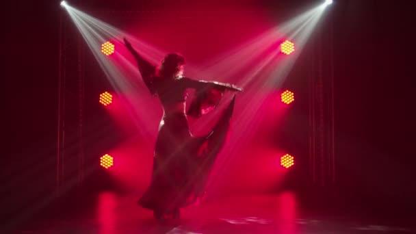 Silueta vášnivé mladé ženy v cikánských šatech tančí a mává dlouhou sukní. Ženské tanečnice tančící romany folk tančí v tmavém kouřovém studiu s červeným světlem. Zpomalený pohyb.