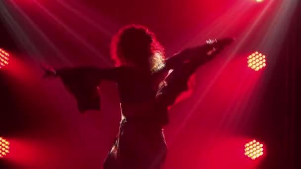 Silueta vášnivé mladé ženy v cikánských šatech tančí a mává dlouhou sukní. Ženské tanečnice tančící romany folk tančí v tmavém kouřovém studiu s červeným světlem. Zavřít. Zpomalený pohyb.