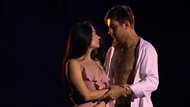 Liebespaar tanzt leidenschaftlich vor dem Hintergrund des Regens in einem dunklen Studio. Tanz der Liebe und Zärtlichkeit. Liebesgeschichte. Schwarzer Hintergrund und weiches blaues Licht. Nahaufnahme.
