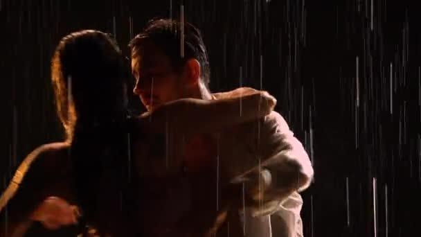 Ein sexy Paar bewegt sich im strömenden Regen im Takt der Musik und liegt dann auf der Wasseroberfläche. Silhouetten von zwei Liebenden. Liebesgeschichte im Tanz. Schwarzer Hintergrund im Studio. Nahaufnahme.