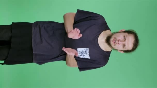 Portrait of a young man looking impatiently at the camera, clapping his hands, and then clenching his fists in joy, screaming a goal. A man in the studio on a green screen. Slow motion. Vertical video