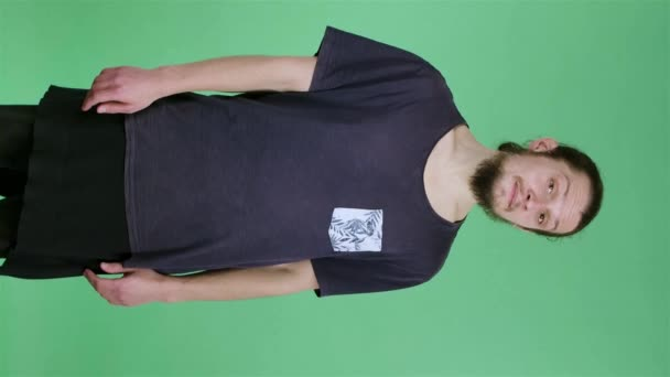 Portrait of a young man who looks at the camera, beckons him with a nod of his head and makes a hand gesture, come here. Bearded guy in the studio on a green screen. Slow motion. Vertical video.
