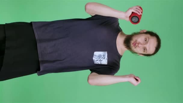 Portrait of a man listening to music with a red portable bluetooth speaker who sings along to the music and dances. A guy in the studio on a green screen. Slow motion. Vertical video.