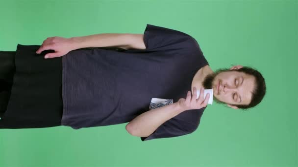 A man in the studio on a green screen holds a cup of coffee and tries a drink. The guy inhales the smell of coffee and drinks it, and then has a disgust for the taste. Slow motion. Vertical video.