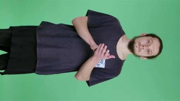 Displeased man claps his hands. Young Caucasian male with a beard in the studio on a green screen background, chroma key. Slow motion. Vertical video.