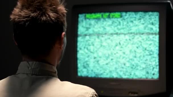 Egy retro TV távirányítóval és médiacsatornával a vállán. Vintage törött TV villogó zaj interferencia vonalak a stúdióban, fekete alapon. Közelről..
