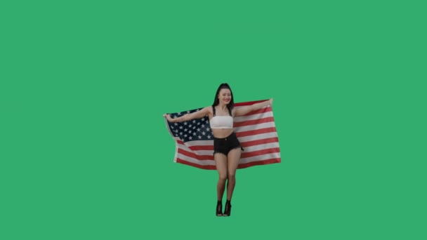Pretty young woman wrapped herself in flag of united states of america. Smiling brunette posing full length against background of a green screen in the studio. Slow motion ready, 4K at 59.94fps.