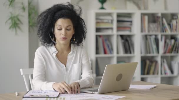 Portrét mladé Afroameričanky mluvící na videokonferenčním hovoru pomocí notebooku a sluchátek, zobrazující mapy. Bruneta sedí u stolu ve světlé domácí kanceláři. Zavřít. Zpomalení připraveno 59.97fps.