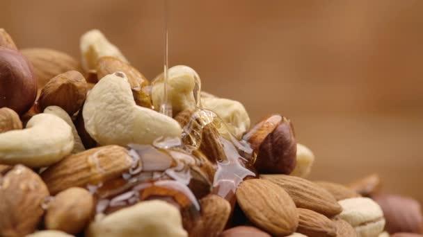 Zpomaleným pohybem stéká po hromadě ořechů pramínek zlatého medu. Med kape a obaluje směs mandlí, kešu a lískových oříšků. Detailní záběr ořechů ve sladkém sirupu.