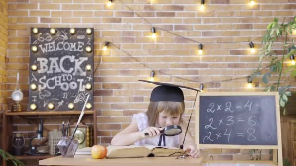 Little girl reads a book with magnifier, sitting at table on background of a school class. An elementary school girl with student black mortarboard cap. School, home education, distance learning.