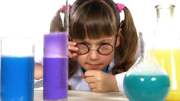 dívka stojí mezi chemické zkumavky