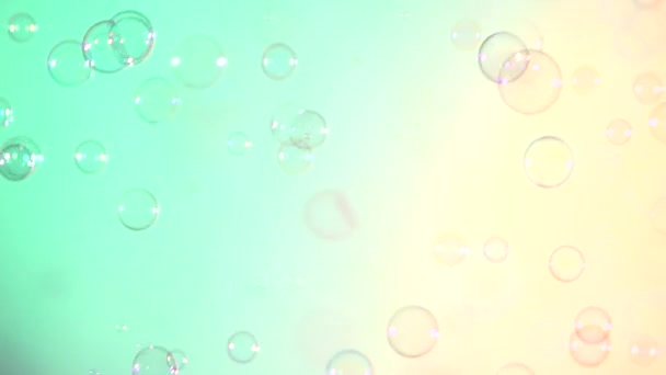 Blue and clear soap bubbles on turquoise and light pink, background