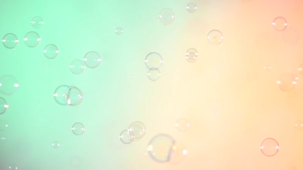 Blue and clear soap bubbles on turquoise and light pink, background, slow motion