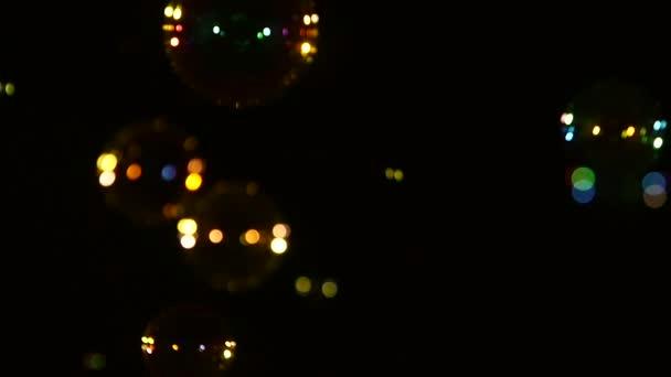 Modré, žluté, hnědé a oranžové mýdlové bubliny na černém, pozadí, zblízka, zpomalené