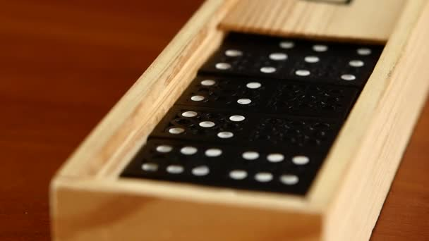 Domino game in closed box, isolated on wooden surface, slow motion