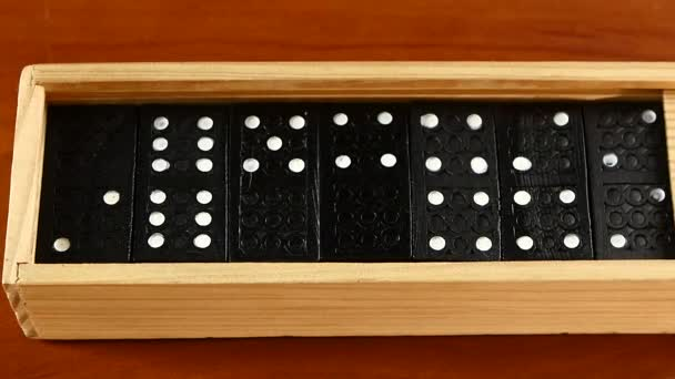 Domino game in open and closed box, isolated on wooden surface, slow motion