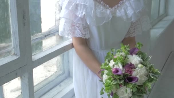 Beautiful girl in vintage white dress sitting on windowsill ond smeling flowers, slow motion