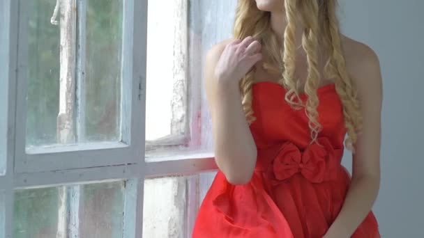 Pretty young woman with wreath of red flowers on her head sitting on windowsill, smiling, cam moves upward, slow motion