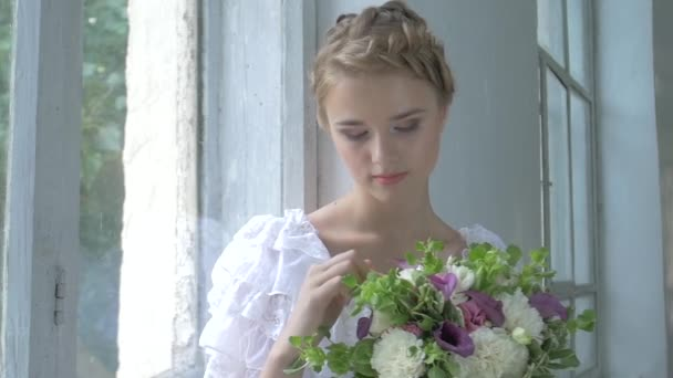 Beautiful girl in vintage white dress sitting on windowsill ond touching flowers, smiling, slow motion