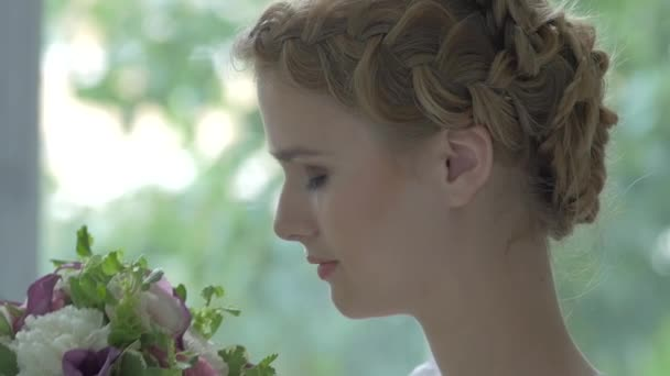 Young blonde girl in white vintage dress enjoys smeling flowers, slow motion