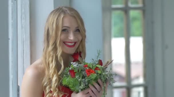 Young blonde girl in red dress smeling flowers, slow motion