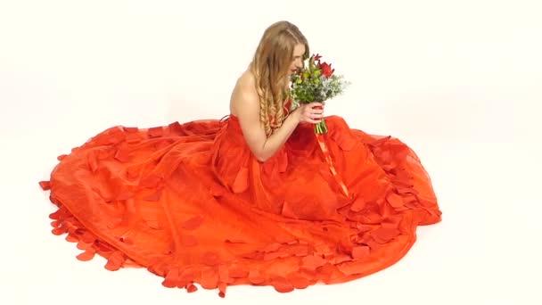 Csinos, fiatal nő ült, gyönyörű piros ruha illata a virágok, a mosolygó, elszigetelt fehér, lassú mozgás