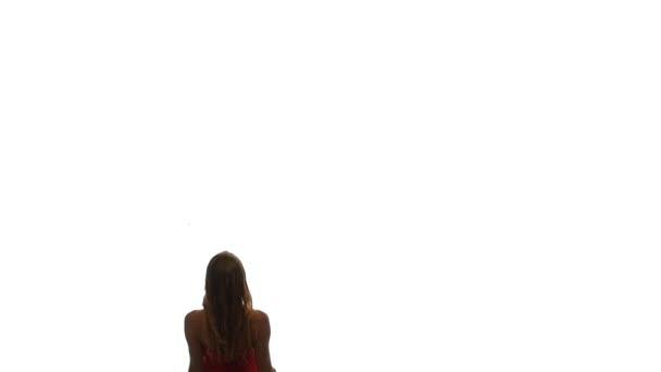 Krásná mladá žena v červených šatech, chůzi, otočí a usmívá se, zpomalené